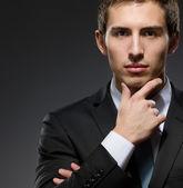 Pensive businessman touches his face — Stock fotografie