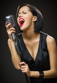 Female musician with closed eyes keeping microphone — Stock Photo
