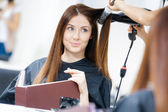 Hairdresser doing hairdo for woman — Stock Photo