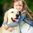 Little girl embraces golden retriever in the park — Stock Photo
