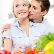 Man kisses pretty girl while she is cooking — Stock Photo