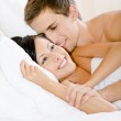 Man lying in bed-room embraces woman — Stock Photo