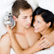 Close up shot of couple lying in bed with alarm clock — Stock Photo
