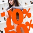 Woman showing the percentage of sales on stylish shoes — Stock Photo #40403287