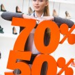 Girl showing the percentage of sales on footwear — Stock Photo #40403387