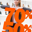 Girl showing the percentage of sales on footwear — Stock Photo