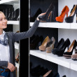 Woman looking at the rows of shoes — Stock Photo #40403563