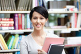 Smiley student with book at the library — Stock Photo