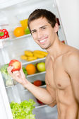 Man hands apple standing near the fridge — Foto de Stock