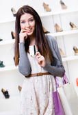 Woman hands credit card in footwear shop — Stock Photo