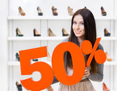 Woman keeps the model of 50 sale on pumps — Stock Photo
