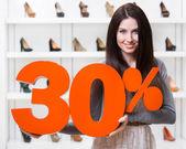 Woman keeps the model of 30 sale on footwear — Stock Photo