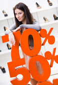 Woman showing the percentage of sales on stylish shoes — Stock Photo