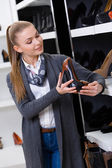 Woman with shoe in hand chooses heeled shoes — Stock Photo