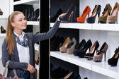 Woman looking at the rows of shoes — Stock Photo