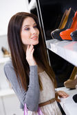 Portrait of woman choosing a pair of footwear — Stock Photo