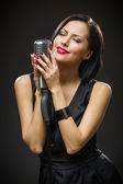 Female singer with closed eyes handing mic — Stock Photo