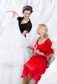 Shop assistant offers another dress to the bride — Stock Photo