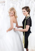 Shop assistant helps to the bride — Stock Photo
