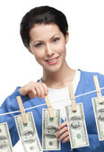 Woman hangs money on the line — Stock Photo