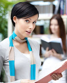Student at the library against bookshelves — Stock Photo