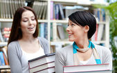 Two girlfriends carry books — Stock Photo