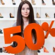 Woman keeps the model of 50 percent sale on footwear — Stock Photo #42680721