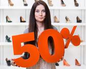 Woman keeps the model of 50 percent sale on footwear — Stock Photo