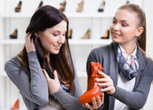 Salesperson offers footwear for the customer — Stock Photo