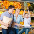 Family against shelves of fruits has shopping — Stock Photo