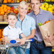 Family against shelves of fruits goes shopping — Stock Photo
