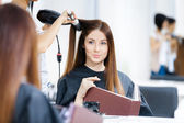 Reflection of beautician doing hairdo for woman — Stock Photo