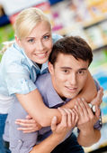 Girl embraces man in the store — Stock Photo