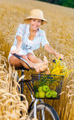 Girl pedals bicycle  in rye field — Stock Photo