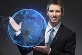 Business man pointing at blue sphere — Stock Photo