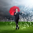 Man with red umbrella and currency signs falling from the sky — Stock Photo #48052533