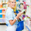 Half length portrait of girl at the market choosing cosmetics — Stock Photo #48052671