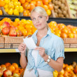 Girl looks through shopping list near the heap of fruits — Stock Photo #48052695