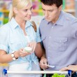 Happy couple discussing the shopping list and chosen products — Stock Photo #48052733