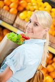 Dívka drží paketů s čerstvou zeleninou — Stock fotografie