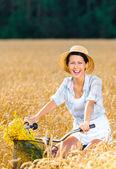 Dívka pedály cyklus s květy v žitné pole — Stock fotografie