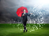 Man with red umbrella and currency signs falling from the sky — Стоковое фото