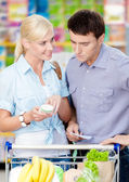 Happy couple discussing the shopping list and chosen products — Stock Photo