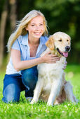 Woman with dog sitting on the grass — Stock Photo