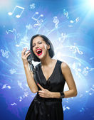 Singer keeping mike against blue music background with notes — Stock Photo