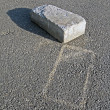 One white abandoned brick with silhouette on grey asphalt. — Stock Photo
