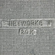 Electric networks as text on vintage metal manhole, telecom. — Stock Photo #13755814