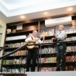 Two vocalists playing on guitar inside of library interior in Kiev, Ukraine. - Stock Photo