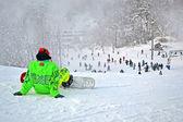 Sportivo in verde suite con salotto skateboard sulla neve bianca. — Foto Stock