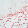 Damaged red yarn grid under white snow, winter season. — Stock Photo